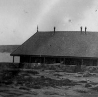 Images: A long stone building surrounded by a low stone fence sits on raised ground overlooking the sea. Part of a coastal land-form is visible in the distance behind the building