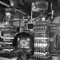 Image: stacks of wine bottles and large wine barrels with signs reading Hardy's