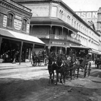 Image: horse drawn vehicles travel down a dirt road lined with terraced shops