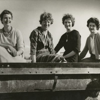 Image: Four smiling women seated on a metal object
