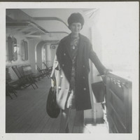 Image: Woman on a boat, posing for a photograph, holding onto the side rail