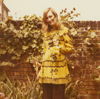 Image: A woman posing for a photograph outside. Behind her is a brick wall covered in vines. She is holding a yellow flower and smiling at the camera.