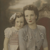 Image: A colour photograph of a young child and her mother. The mother is sitting on a chair, the girl is standing to her left