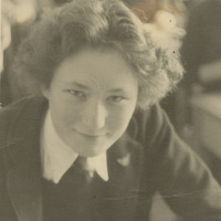 """Image: Photographic portrait of a young woman in school uniform. She has a book open in front of her. The photo is inscribed in blue pen: """"To Nanny, With Love, Barbara"""""""