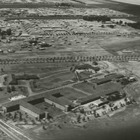 Image: An aerial view of several large buildings arrayed in rows in a largely flat, agricultural landscape