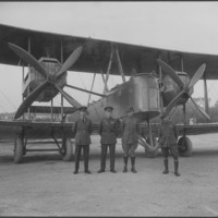Image: Four men standing in front of a bi-plane