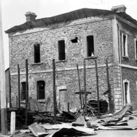 Image: A two-storey stone building with burned out windows and melted roof cladding. The burnt remains of another building are in the foreground