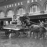 Image: A horse-drawn cart passes in front of a large brick building with the words 'Federal Hall' in large letters on its front facade
