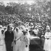 Image: Black and white photograph of a large crowd standing behind a group of women dressed in white and a man in a dark suit. In the centre of the picture a wounded soldier can be seen in a stretcher bed.