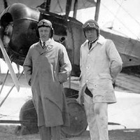 Image: Two men wearing suits, overcoats and early-twentieth century aviator helmets pose for a photograph in front of a biplane