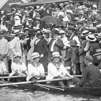 Image: A large crowd watches four female rowers and their male cox