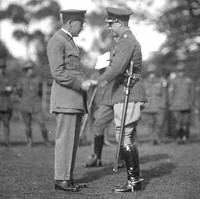 Image: Two men in military uniforms shake hands on an open field. A group of Australian Army soldiers stand in a line in the background