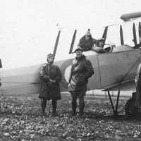 Image: A group of men and one woman stand around a biplane. The identification number 'H3033' is painted on both the tail and side of the aircraft
