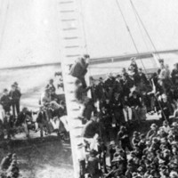 Image: A large crowd of men gather on a wharf to hear a speech
