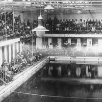 Image: A crowd of people in early twentieth century attire are gathered at the side of a large swimming pool