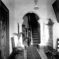 Image: the entry hall of a house. The decorative tiled floors are covered by a runner carpet which extends through an archway supported by columns and up a narrow staircase.