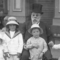 Image: Black and white photograph of seated man, wearing a top hat, surrounded by four small children. In the background a woman stands near a table facing away from the camera.