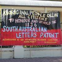 Image: large banner with message painted in yellow and white over a red and black background