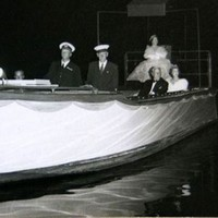 Image: a woman in an extravagant gown sits on a raised dias at the stern of a small boat. Other well dressed individuals sit along the sides of the boat.