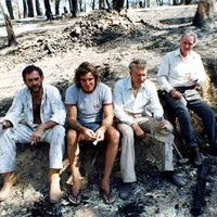 Image: four men sitting in burnt out bushland
