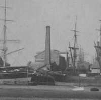 Image: A multi-storey stone building with large brick chimney sits near a river-front wharf. A larger chimney is located to the right of the building, and several ships are moored at the wharf