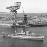 A warship gets underway in waters a short distance from a shore-based shipbuilding facility. The facility includes two large cranes and several buildings