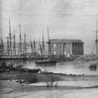 Image: A number of sailing ships are moored in a river. A cluster of buildings and wharves are visible in the background. A rowboat discharges people in the right foreground