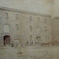Image: A large, imposing three-storey nineteenth century warehouse stands near a port waterfront. Horse-drawn carts are positioned near large doors at the front of the building, and the masts of a sailing ship are visible in the distance