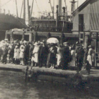 Image: A large group of people congregate on a floating dock next to a wharf. A steamship and warehouses are visible in the near background