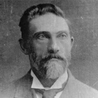 Image: Photographic head-and-shoulders portrait of a bearded, middle-aged Caucasian man. He has a full head of hair, light-coloured eyes and is wearing an Edwardian-era suit and tie