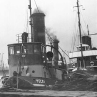 Image: A line of three tugboats tied up at a wharf. The tug in front has the name 'Yelta' painted on its bow