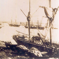 Image: A sailing ship is tied up alongside a long wharf. Horse-drawn carts full of cargo are positioned on the wharf next to the ship. Other sailing ships are visible in the background