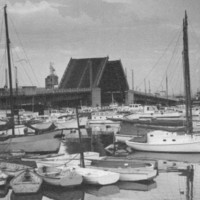 Image: A drawbridge within an active port is open to allow a vessel to pass beneath it. Several sail-boats and other small watercraft are moored in a boat basin in the foreground