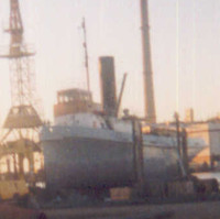 Image: A derelict tugboat in drydock at a boatyard. A large crane and a building with two tall chimneys is visible in the background