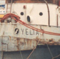 Image: A derelict tugboat is moored against a wharf. A handful of other small boats are also moored at the same wharf