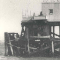 Image: A metal lighthouse with a large wooden support platform stands surrounded by water. The platform appears to be in a state of disrepair along one of its sides