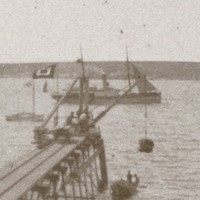 Image: A small wooden jetty projects into the ocean from a rocky coastline. A small steam vessel, four small sailboats and another island are visible in the background