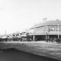 Image: The intersection of two dirt streets in a relatively large town. People dressed in early twentieth century attire walk along the street among several horse-drawn carts and carriages