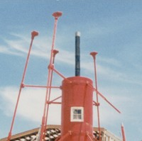 Image: The bottom section of a bright red, pre-fabricated 1860s-era lighthouse under construction. A large warehouse building is under construction in the immediate background