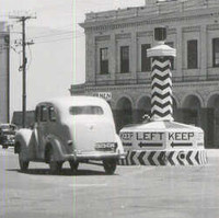 Image: Cars of 1950s vintage pass around a large plinth in the centre of an intersection in an urban area. The words 'Keep Left' are painted on the plinth, as are several large left-facing black arrows