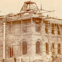 Image: An imposing, two-storey stone building under construction. The building is surrounded by scaffolding and a handful of men stand in front of its ground floor