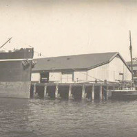 Image: A large steamship and two small sailing vessels are tied up at a wharf. A number of buildings are visible in the background