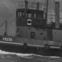 Image: A tugboat with 'Yelta' painted on its bow underway in an active port. A number of large ships and a wharf are visible in the background