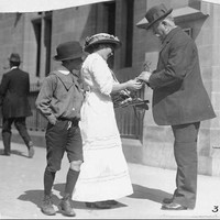Image: A woman is selling some wattle plant to a man in the street as a young boy looks on, a man walks by in the background