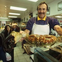 Image: man holding large crab in front of him with people looking on
