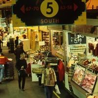 Image: groups of people walking through market stalls
