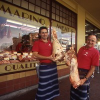 Image: two men holding meat in front of butchers shop
