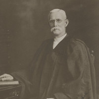 Image: Man dressed in robes, with large white moustache and glasses sits on a chair by a desk with his hand on a bible
