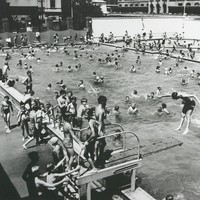 Image: large number of children in and around swimming pool