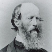 Image: a head and shoulders portrait of a man in three quarter profile. He is balding but has a long bushy beard.
